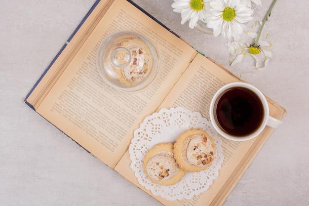 Haferflockenplätzchen und eine tasse tee auf offenem buch.