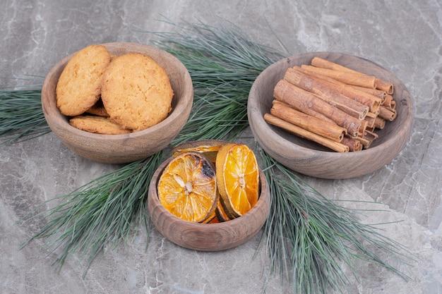 Haferkekse auf einer holztasse mit zimt und orangenscheiben