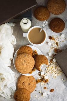 Haferkekse, bücher, haferflocken, tasse kaffee mit milch, rosinen auf einer hellen oberfläche. das konzept von guten morgen und frühstück. draufsicht