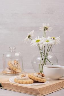 Haferkekse, eine tasse und gänseblümchen auf buch.