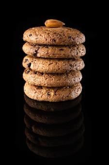 Haferkekse mit schokoladenstückchen sind auf schwarzem hintergrund mit einer reflexion isoliert. viele braune runde hausgemachte kekse liegen auf einer reflektierenden oberfläche, nahaufnahme.