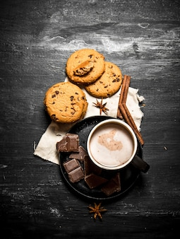 Haferkekse mit schokoladenstücken und kakao trinken. auf einem schwarzen holztisch.