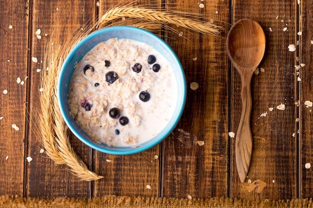 Hafermehl mit johannisbeere in der blauen schüssel mit löffel auf hölzernem hintergrund. rustikaler stil. gesundes frühstück. ansicht von oben.