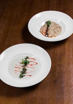 Hafermehl mit nüssen, soße und grünen blättern in den weißen platten auf dunklem hölzernem hintergrund in ar