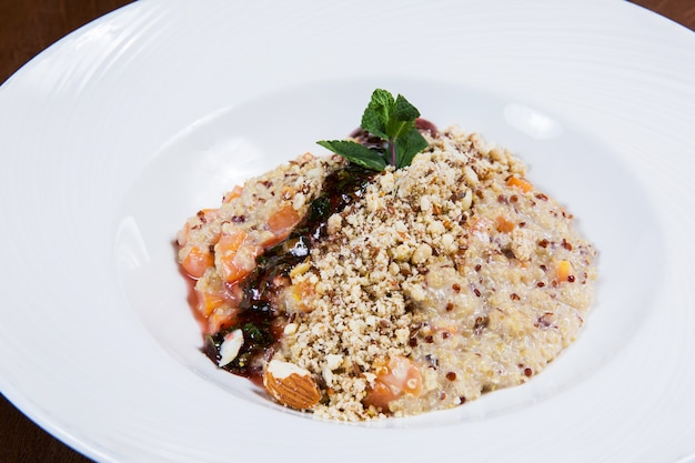 Hafermehl mit nüssen und soße in der weißen platte auf dunklem holztisch in einem restaurant. leckeres gesundes essen