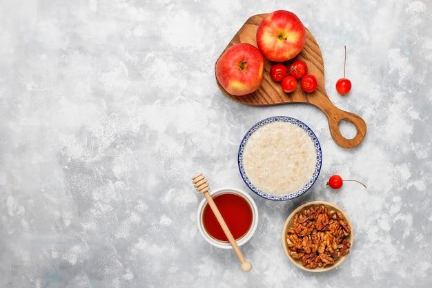 Hafermehlbrei in einer schüssel mit honig und roten apfelscheiben, draufsicht