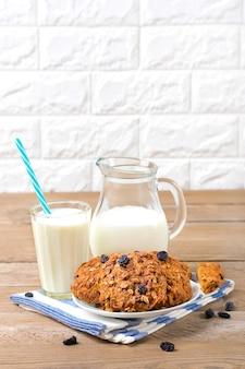 Hafermehlplätzchen mit getreide und rosinen, milch in der flasche und im glas auf hölzernem hintergrund, gesunder snack.