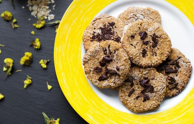 Hafermehlplätzchen mit schokolade auf gelber platte