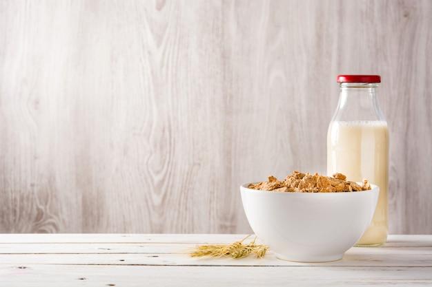 Hafermilch und müsli auf weißem holztisch