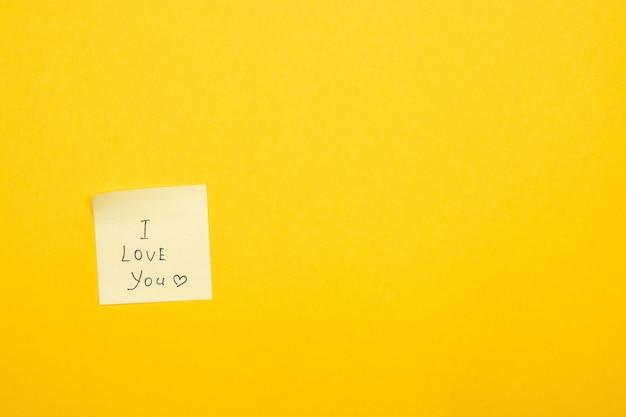 Haftnotiz auf gelber wand, die sagt, ich liebe dich