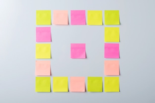 Haftnotizen in verschiedenen farben in form eines quadrats an einer grauen wand.