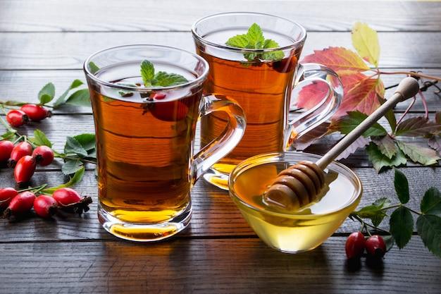 Hagebutten-tee in transparenter tasse mit honig und frischen beeren. vitamin c getränk auf dunklem tisch