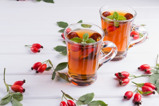 Hagebutten-tee in transparenter tasse mit honig und frischen beeren. vitamin c getränk auf weißem tisch
