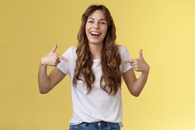 Haha, grossartig. positive aufrichtige attraktive junge frau lockiges langes haar lachend freudig zeigend finger zentrum kopie raum weißes t-shirt kichern spaß diskutieren tolle link zeigen sie promo