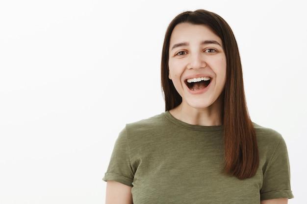 Haha, so lustig. porträt eines amüsierten und sorglosen mädchens, das spaß daran hat, mit offenem mund laut zu lachen und entzückt und unterhalten auszusehen, während es eine lustige fernsehsendung sieht und über eine graue wand scherzt