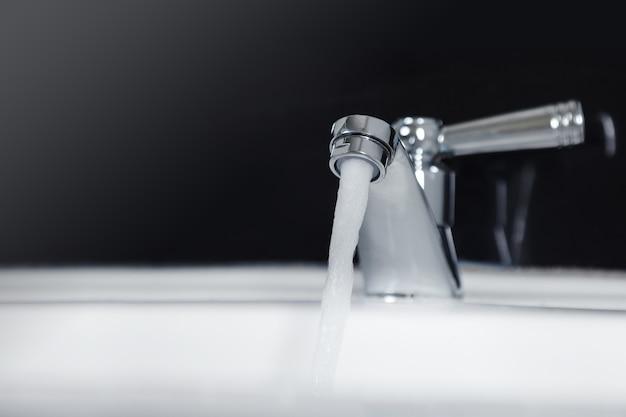 Hahn und wasser fließen auf badezimmer