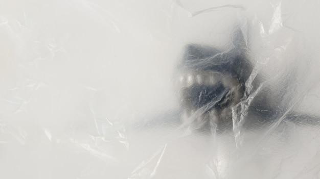 Hai (spielzeugmodell) hinter dem transparenten und zerknitterten kunststoff mit kopierraum. kreativer konzepthintergrund für umweltschutz und kunststoffbewusstsein.