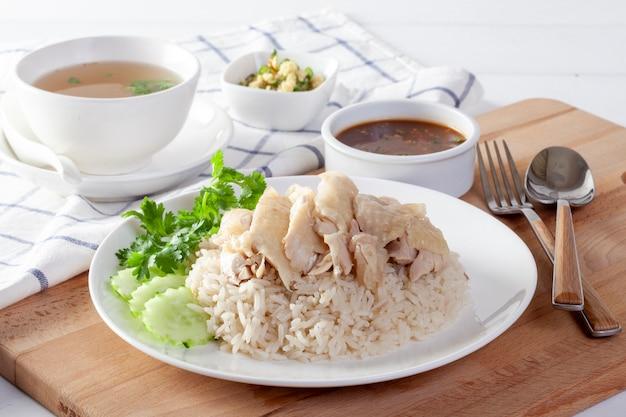 Hainanese-hühnerreis, gedämpftes huhn mit reis, khao mun kai auf hölzernem hintergrund