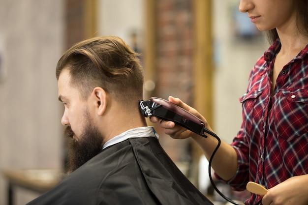 Hairstylist frau macht haarschnitt
