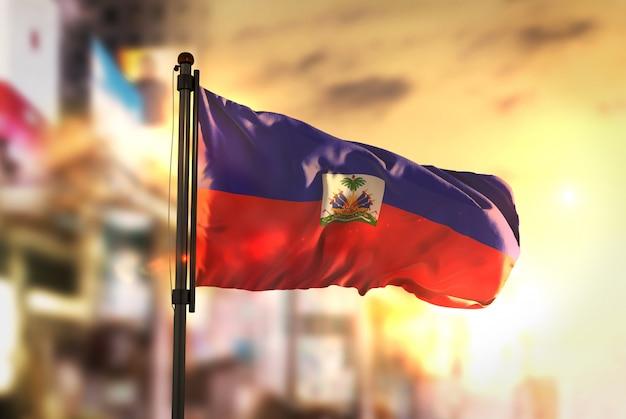 Haiti-flagge gegen stadt verschwommen hintergrund bei sonnenaufgang hintergrundbeleuchtung