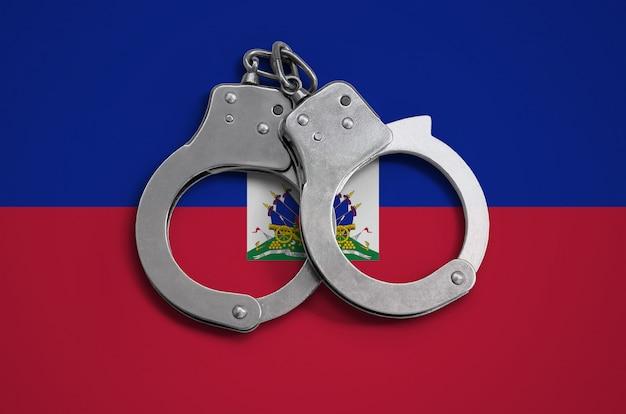 Haiti flagge und polizei handschellen. das konzept der einhaltung des gesetzes im land und des verbrechensschutzes