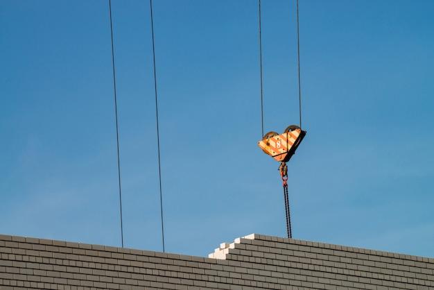 Haken des turmkrans über unvollendetem gebäude auf der baustelle. bild der weißen backsteinmauer unter blauem himmel.