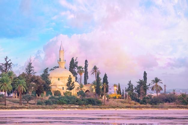 Hala sultan tekke moschee am ufer eines salzsees in larnaca, zypern. am frühen morgen, rosa morgendämmerung