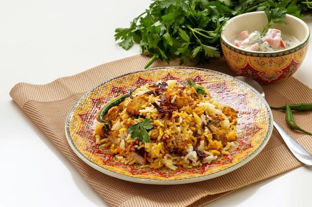 Halal indisches huhn biryani serviert mit joghurt tomate raita