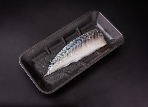 Halb frischer thunfisch in scheiben geschnitten auf schwarzer schaumstoffeinlage auf schwarzem hintergrund isoliert, thunfisch zum verkauf, ansicht von oben.
