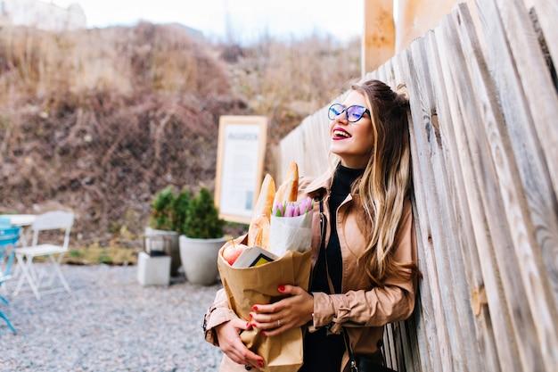 Halb gedrehtes foto der attraktiven frau mit papiertüte des leckeren essens vom supermarkt. charmantes mädchen, das frische lebensmittel zum mittagessen mit ihrer familie trägt, die mit verträumtem gesichtsausdruck aufwirft.