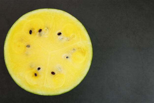 Halb gelbe wassermelone auf schwarzem