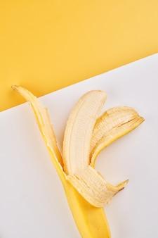 Halb geschälte banane auf gelbem weißem hintergrund mit kopienraum
