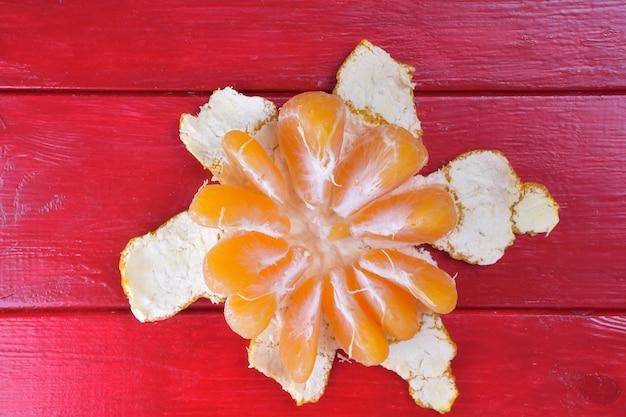 Halb geschälte mandarine liegt auf einem leuchtend roten holzhintergrund in der mitte des rahmens