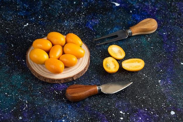 Halb geschnitten und dabei kumquats auf blauer oberfläche