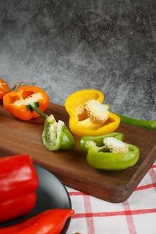 Halb geschnittene bunte paprika auf einem holzbrett.