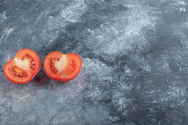 Halb geschnittene frische bio-tomate auf grauem hintergrund. hochwertiges foto