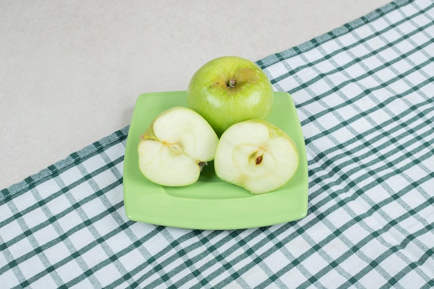 Halb geschnittene grüne äpfel auf grünem teller