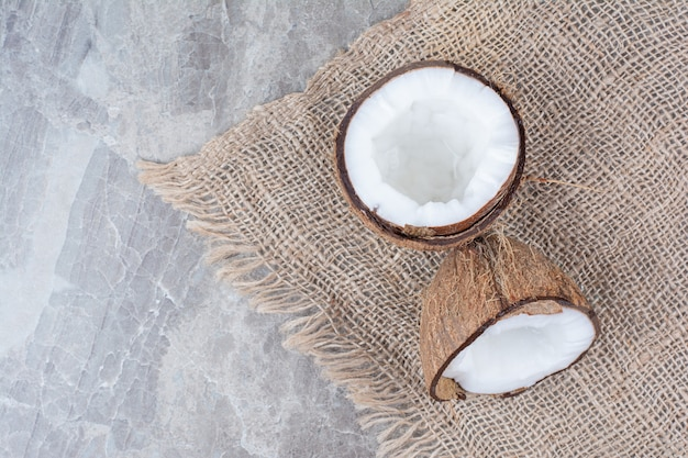 Halb geschnittene kokosnüsse auf steinoberfläche mit sackleinen.