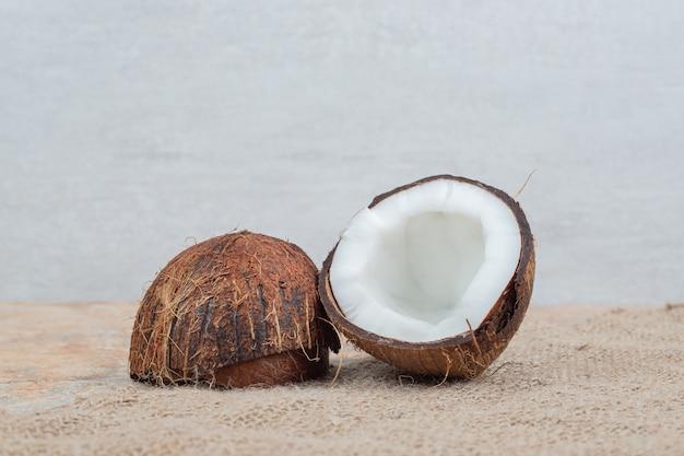 Halb geschnittene reife kokosnüsse auf marmortisch mit sackleinen.