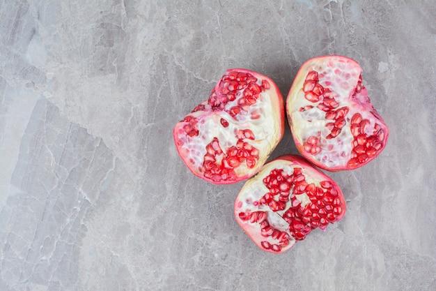 Halb geschnittene rote granatäpfel auf steinhintergrund.