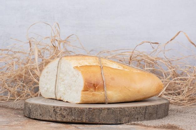 Halb geschnittenes brot mit seil auf holzstück gebunden