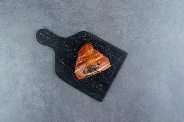 Halb geschnittenes croissant mit schokolade auf schwarzem brett.