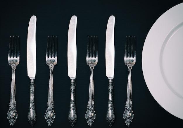 Halb leere weiße platten, weinlesemesser und gabel auf tabelle