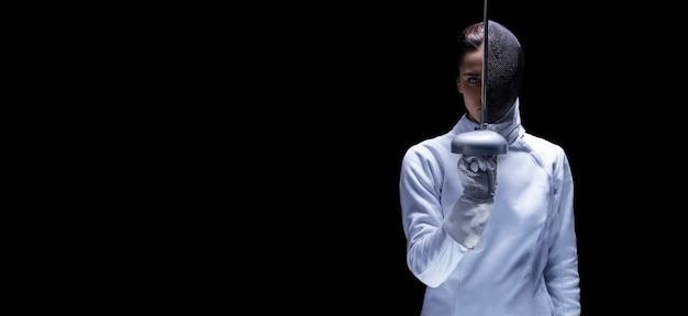 Halb maskiertes fechtermädchen im kostüm posiert mit dem schwert in der hand