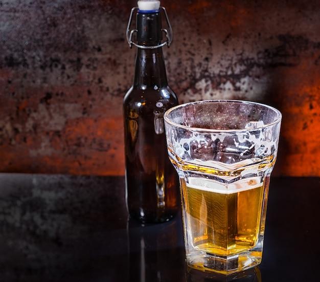 Halb volles glas bier und bierflasche auf schwarzer spiegelfläche. lebensmittel- und getränkekonzept