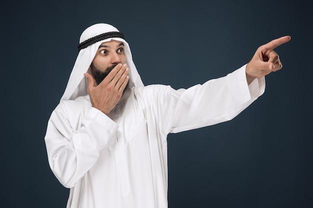Halbbild des arabischen saudischen geschäftsmannes. junges männliches model erstaunt, zeigt oder wählt. konzept von geschäft, finanzen, gesichtsausdruck, menschlichen emotionen.