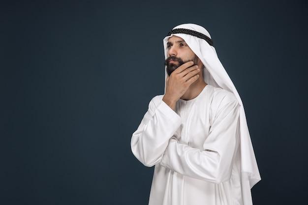 Halbbild des arabischen saudischen geschäftsmannes. junges männliches modell stehend und sieht nachdenklich aus. konzept von geschäft, finanzen, gesichtsausdruck, menschlichen emotionen.