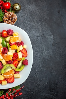 Halbe aufnahme der sammlung von frischen früchten auf tellerdekoration zubehör tannenzweige ein auf dunklem hintergrund