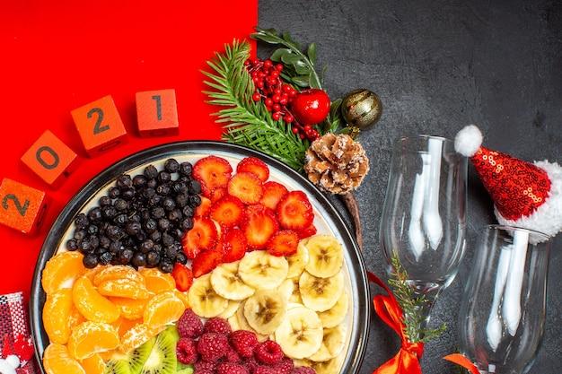 Halbe aufnahme der sammlung von frischen früchten weihnachtssocke sant laus hut zahlen glaus becher auf dunklem hintergrund