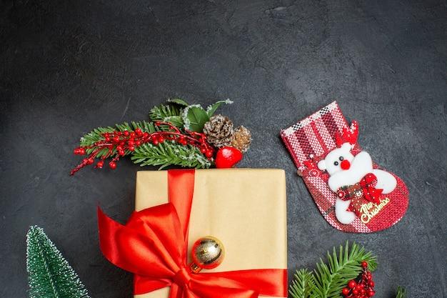 Halbe aufnahme der weihnachtsstimmung mit schönen geschenken mit bogenförmigem band und tannenzweigdekorationszubehör-weihnachtssocke auf einem dunklen hintergrund